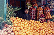 AFG89LEE5_14 Boy vendor stands behind market stall laden with oranges; pomegranates, apples, fruit trade. Kabul, Afghanistan.