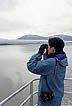 ALA94LS3_15 Ecotourism: UK woman looks through binoculars out across water at Taku Inlet, whale watching area. Alaska. Copyright Tropix (Lynn Seldon)