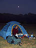 ARG07RB038 German woman (25)  tent at dawn; moon in dark sky. Los Cardones National Park, Salta Rgn, Argentina. MODEL RELEASED. Copyright Tropix (Roland Birley)