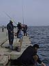 AZB07VJB188 Men fishing off jetty with rod and line; the Bulvar, Caspian Sea front; Sunday. Baku, Azerbaijan. Copyright Tropix (V. and M. Birley)