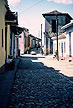 CUB87ASH7_16 Men sit in narrow band of shade by pastel painted houses (yellow, pink) on cobbled street; people beyond. Trinidad, Cuba Copyright Tropix (A & S HIGGINS)