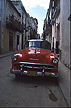 CUB99LUM3_15 Red Chevrolet classic car in good shape parked in narrow street of old housing; balconies, pastel walls. Havana, Cuba. Copyright Tropix (Stuart Lumb)