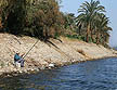 EGY09VJB063 Fisherman sitting on stone embankment preparing line; date palms; flotsam litter on shore of River Nile; Luxor, Egypt. Copyright Tropix (V. and M. Birley)