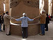 EGY09VJB523 German tourists hold hands encircling huge column in Hypostyle Hall, Temple of Karnak, Luxor (ancient Thebes), Egypt. Copyright Tropix (V. and M. Birley)