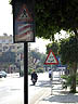 EGY09VJB778 Road signs warn drivers of pedestrian crossing; motorbike; bicycle; air pollution haze; the Corniche, Luxor, Egypt. Copyright Tropix (V. and M. Birley)