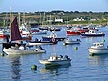 ENG06MHB181 Colourful boats on beach, low green hill; seafront houses. Hughtown, St Marys, Isles of Scilly, England. Copyright Tropix (M & V BIRLEY)