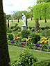 ENG09VJB377 Lawn of landscaped garden with marble statue gives way to small hill & topiary. Hampton Court Palace, Surrey, England. Copyright Tropix (V. and M. Birley)