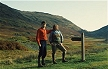 ENG92TX15_21 Couple stand with walking gear on next to sign post; hills behind; hiking, fell walking. Lake District, Cumbria, England Copyright Tropix (V. and M. Birley)