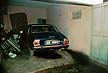 GHA90LB6_01 Car in garage discharges black exhaust fumes, driver preparing to reverse; oil leak puddle; pollution. Accra, Ghana. Copyright Tropix (L. BRYDON)