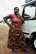 GHA93TX10_12 Obese funeral parlour manageress wears red T-shirt and wrap for mourning, business woman, by 4x4 car; Accra, Ghana. Copyright Tropix (V. and M. Birley)