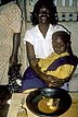 GHA93TX11_17 Woman holds boy on lap; half eaten meal of fufu (cassava & plantain) & rodent meat on table. Atipoku, E Region, Ghana. Copyright Tropix (V. and M. Birley)