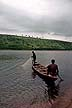 GHA93TX57_06 Two fishermen in canoe, one draws in cast net, other paddles; early evening. Akasombo Port, inlet off Lake Volta, Ghana. Copyright Tropix (V. and M. Birley)
