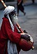 IND90DJ2_17 Old man, beggar, Osho sannyasin (meditation cult) costume, plays stringed musical instrument. Pune, Maharashtra, W.India Copyright Tropix (D. Jenkin)