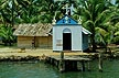 IND90DJ6_20 Roman Catholic chapel, blue roof, thatched roof, on edge of river, quay, viewed from ferry; palm trees. Kerala, S.India. Copyright Tropix (D. Jenkin)