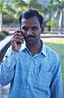 IND97TX2_06 Young man, Hindu caste mark, moustache, makes call on mobile phone, excited expression. Aurangabad, Maharashtra, India. Copyright Tropix (V. and M. Birley)