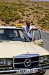 MOR03TX10_14 Arabic taxi driver and his Mercedes on edge of highway, leans out of open door. Morocco. Copyright Tropix (V. and M. Birley)