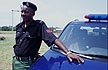 NIG06TX5_20 Police sergeant, uniform, revolver in holster, by car; security; emergency services; Folu, Lagos State, S.Nigeria. Copyright Tropix (V. and M. Birley)