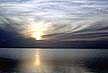 NIG69RC3_19 Cirrus cloud over still water, pale gold sun obscured; dawn; pearly grey sky, reflected light. Lake Chad, Nigeria. Copyright Tropix (R. CANSDALE)