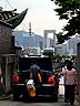SKO07VJB130 Contrast: man unloading shopping, big car, in narrow street of traditional houses; modern high rises. Seoul, S.Korea. Copyright Tropix (V. and M. Birley)