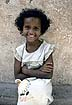 SOM85PF1_02 Smiling young Somali girl; missing tooth, fluffy hair, fly on forehead; from Hargeisa (Hargeysa) Orphanage. Somalia. Copyright Tropix (P. Frances)
