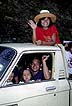THA88TX5_15 Informal settler family laughs in pick-up truck: dad smokes, kids on lap; mum waving. Chiew Larn, Surat Thani, Thailand. Copyright Tropix (V. and M. Birley)