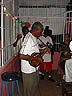 TRN07RB043 Old, black, Mandolin player, Parang band, performing in bar, ballons; security door. Petersville, Trinidad. Copyright Tropix (Roland Birley)
