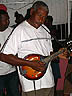 TRN07RB046 Old, black, Mandolin player, in white tee shirt looking serious, Parang band, performing in bar. Petersville, Trinidad. Copyright Tropix (Roland Birley)
