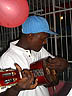 TRN07RB048 Cuatro guitar player in blue cap, white shirt; red balloon, security door; Parang music, bar. Petersville, Trinidad. Copyright Tropix (Roland Birley)