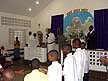 TRN07RB143 Choirboys standing, singing, clapping hands; Minister, Bishop; Mount Zion Spiritual Baptist Church; Pinto, Trinidad. Copyright Tropix (Roland Birley)