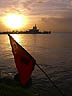TRN07RB223 Hindu prayer flag tilting in sea, white setting sun in reddish sky. Silhouetted Temple In The Sea. Waterloo, Trinidad. Copyright Tropix (Roland Birley)